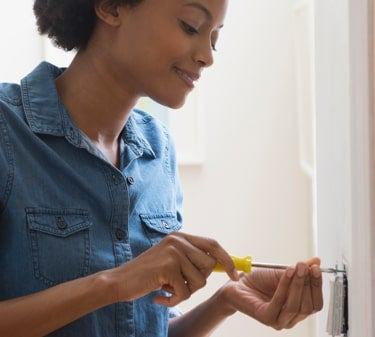 Woman installing a DIY home security system