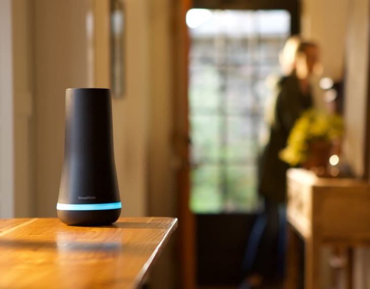 Black SimpliSafe detector on a table with a person in the background